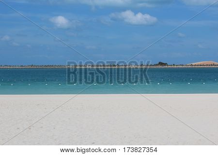 beige sand and blue water with a cloudy sky