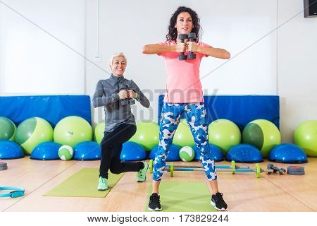 Two Caucasian women doing exercises with dumbbells working out indoors in aerobics class.