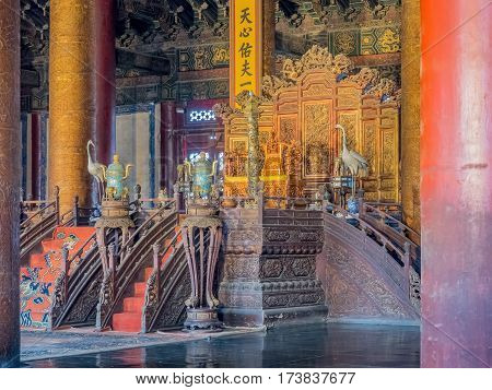 Beijing, China - Oct 30, 2016: Emperor`s throne and court area in the Hall of Supreme Harmony Taihedian. Forbidden City Gu Gong, Palace Museum. Rare low light view, no flash allowed.