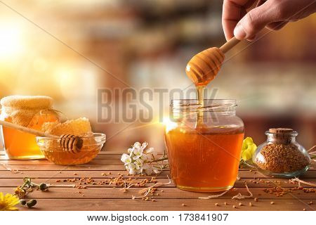 Hand With Dipper Picking Honey From A Jar Of Honey
