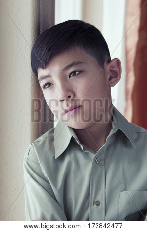 Boy appears to be day dreaming by a window.