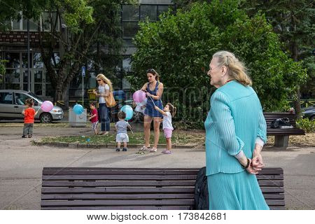 BELGRADE SERBIA - AUGUST 2 2015: Old woman looking at younger women taking care of children playing with balloons in the suburb district of Zemun