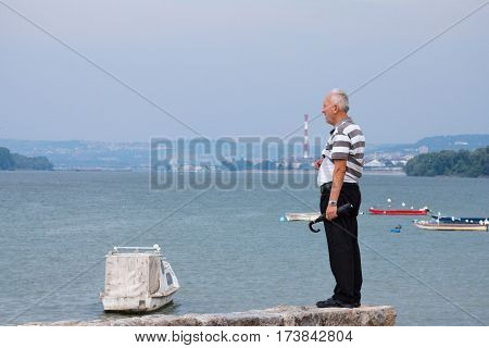 BELGRADE SERBIA - AUGUST 2 2015: Old man observing Belgrade center and the Danube from the suburb of Zemun on a cloudy day