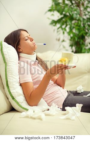 Cold girl lying on the couch with a thermometer in her mouth