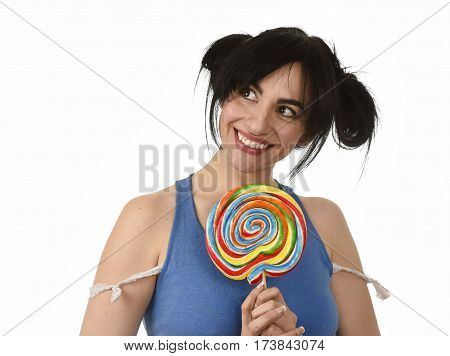 sexy and happy seductive woman with ponytails and blue top holding and licking sweet caramel big lollipop isolated in white background with naughty playful face expression