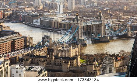 London city center with most know famous town attraction lifting Tower Bridge over river Thames. Tower of London in from of the view is under a sunshine rays. Residential buildings and offices surround main historical buildings.
