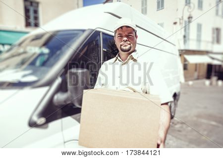 Messenger delivering parcel, standing next to his van in urban setting