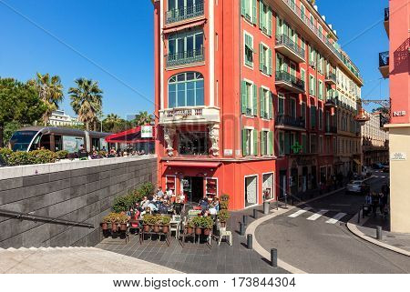 NICE, FRANCE - MARCH 26, 2016: Unusual red building and outdoor restaurant on Place Massena in Nice - fifth most populous, second-largest and one of the most French city on Mediterranean coast.