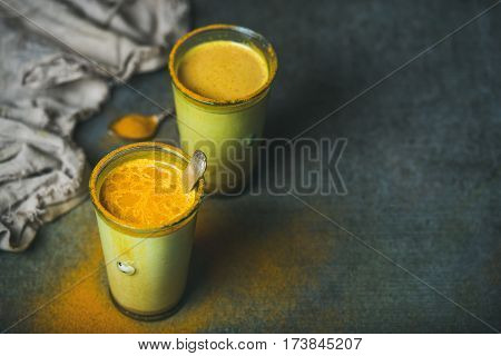 Golden milk with turmeric powder in glasses over dark grunge background, copy space. Health and energy boosting, flu remedy, natural cold fighting drink. Clean eating, detox, weight loss concept
