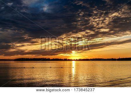 Oklahoma sunset over the lake with some ducks swiming along.