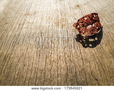 A decay brown leaf under sunlight casting shadow on on wood top.