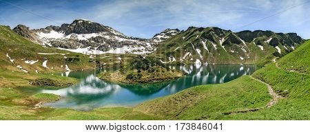 Remote Schrecksee lake up high in the alpine mountains in spring or summer. The island in the lake is inaccessible by foot. Bavaria, Allgau, Germany.