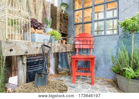 Red chair at green garden with cosy house. Outdoor garden.