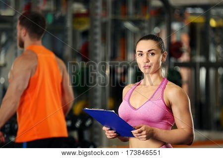 Personal trainer holding clipboard with training plan in gym