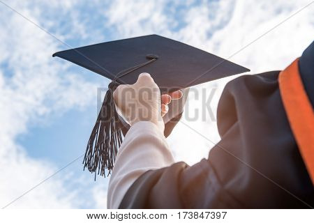 Graduates of the UniversityOf graduates holding hats handed to the sky.