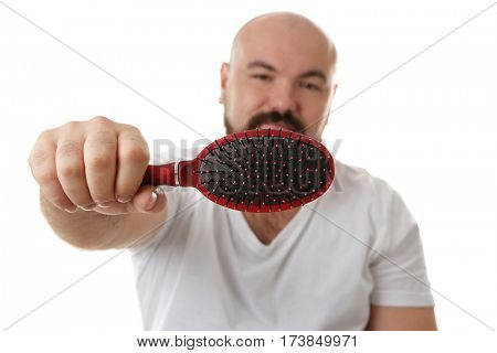 Bald adult man with hair brush on white background