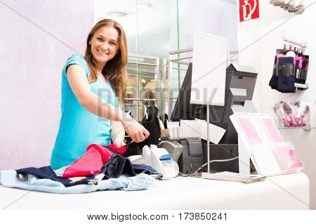 salesperson standing at cash register in fashion store