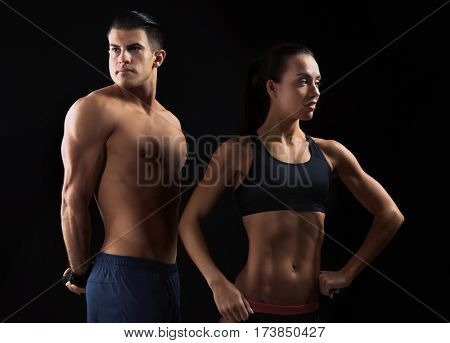Sporty young couple on black background