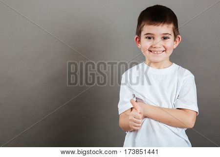 Smiling little boy standing and showing thumbs up