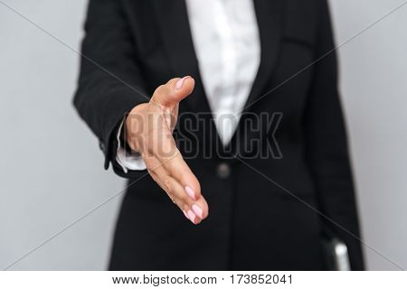Cropped image of business woman in suit which extends hand at camera