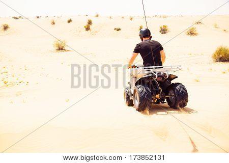 tourist riding a quad bike in the desert