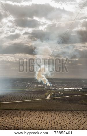 Column of smoke, expelled by an industry or farm, in the middle of a rainfed farm