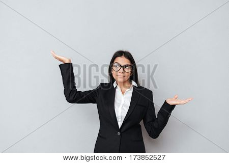 Portrait of a serious businesswoman in eyeglasses holding copyspace on two palms isolated on a gray background