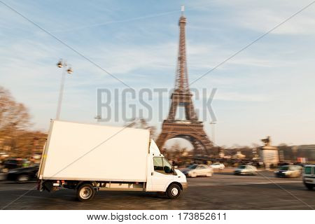 white delivery van driving past the eiffel tower. the van is sharp, rest is motion blurred.