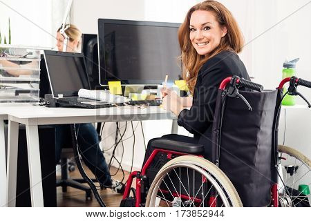 a woman sitting in a wheelchair is working in a modern office