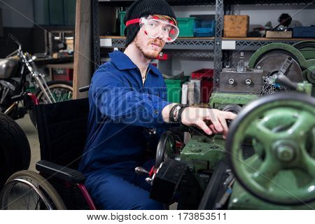 young mechanic apprentice in wheelchair working on turning lathe