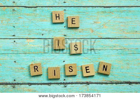He Is Risen Christian Blocks On A Blue Wood Plank Background