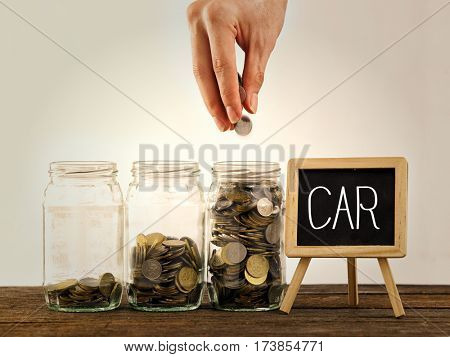 hand putting a coin into glass bottle, saving concept and a mini blackboard with text car
