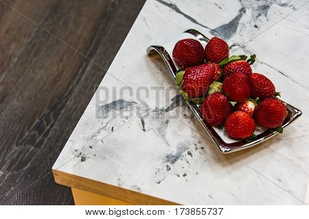 part of modern kitchen counter made of granite natural stone, white worktop with gray grains carrera marble