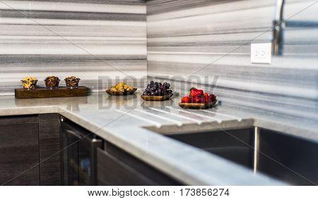 Kitchen countertop. Kitchen granite countertop with backsplash. Fruits on kitchen countertop. Custom granite kitchen countertop with stainless steel sink.