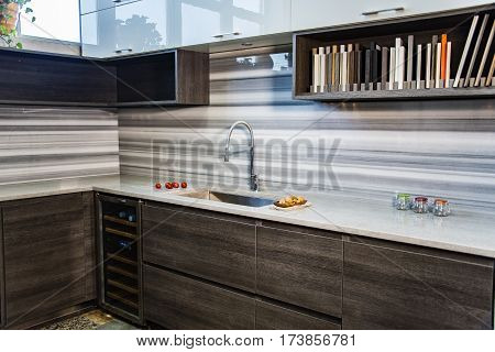 a new kitchen design, modern kitchen in home with bamboo wood cabinetry and countertop designed with full high stone backsplash