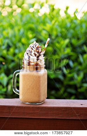 Chocolate frappe coffee with whipped cream and syrup outside on a summer day