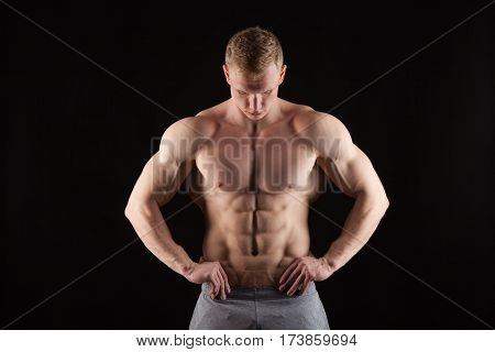 Athletic handsome man fitness-model showing six pack abs. isolated on black background with copyspace.