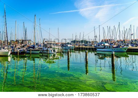 Sail boats and motor boats moored in a part of the harbor overtaken by algae in the historic fishing village of Urk in the Netherlands