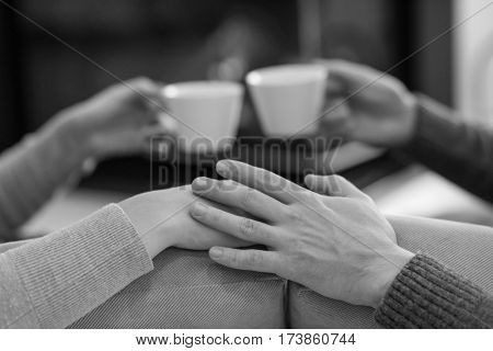 Young romantic couple sitting on sofa in front of fireplace at home, looking at each other, talking and drinking coffee autumn day