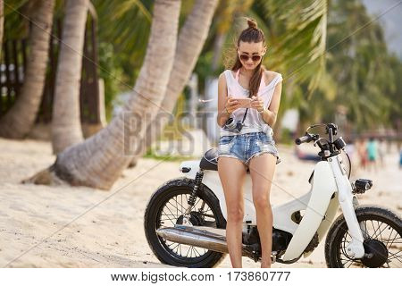 woman using smartphone beside motorbike in thailand