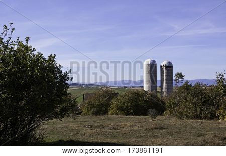 Quebec City, Quebec,September 26, 2016 -- Two silos loom large at the front of a large farm off the Trans Canada Highway north of Quebec City Quebec with the mountains along the shore of Baie Saint Paul in the background on a bright sunny blue sky day