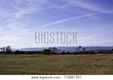 Wide view of cut corn field landscape off the Trans Canada Highway north of Quebec City, Quebec with the mountains along the shore of Baie Saint Paul in the background on a beautiful, bright sunny blue sky day in September.