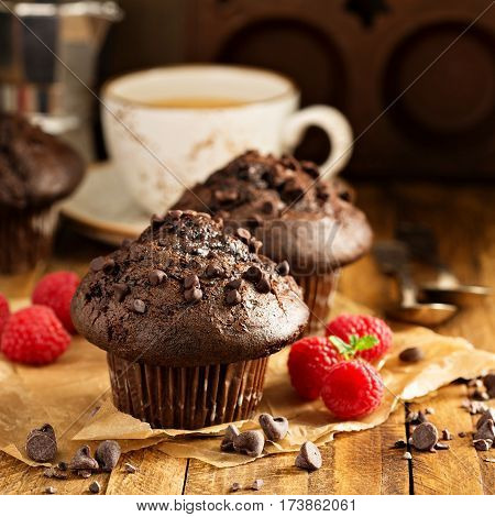 Double chocolate muffins with raspberry and a cup of coffee in a rustic setting
