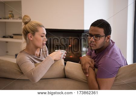 Young romantic multiethnic couple sitting on sofa in front of fireplace at home, looking at each other, talking and drinking coffee