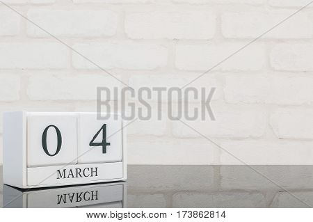 Closeup white wooden calendar with black 4 march word on black glass table and white brick wall textured background with copy space selective focus at the calendar