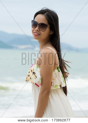 Portrait of young beautiful asian woman wearing sunglasses and standing on the beach. Summer time relaxation or vacations concept