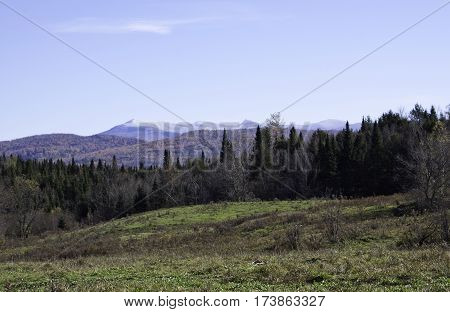 Wide view of Sutton peaks with autumn trees of colorful fall foliage on a beautiful bright sunny day in October near the town of Sutton in the Eastern Townships of Quebec.