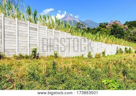 Boundary wall with sugar cane field & Fuego & Acatenango volcanoes behind in Escuintla, Guatemala, Central America