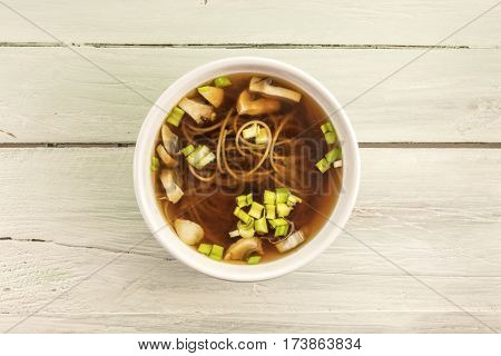 A photo of a miso soup with buckwheat soba, champignons, and green onions, shot from above on a wooden background texture with copy space