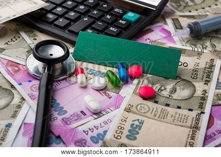 healthcare in india concept - showing indian new currency notes of rupees 500 and 2000 in the background with colourful pills, stethoscope, calculator, injection, and blank card